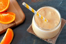 Orange Smoothie In A Glass With Striped Straw And Fruit Slices