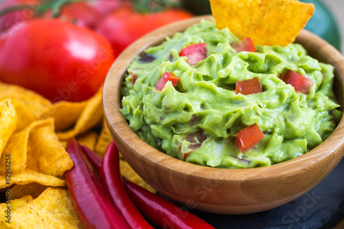 Fotografie, Obraz  Guacamole in Wooden Bowl with Tortilla Chips and Ingredients