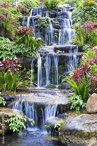 Fototapeta Artificial waterfall and statue at the garden