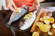 Close-up of housewife putting pieces of lemon in fish