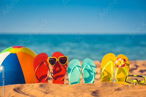 Flip-flops, beach ball and snorkel on the sand