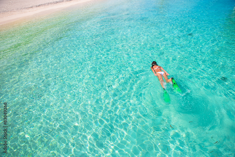 Fototapeta Young girl snorkeling in tropical water on vacation