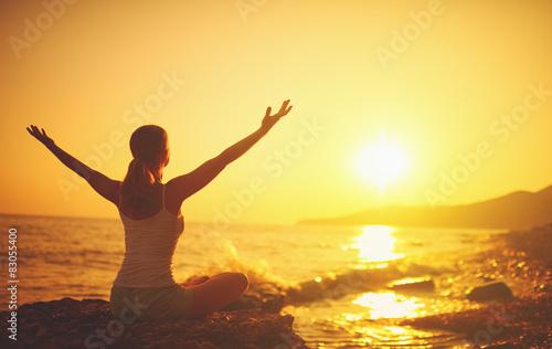 yoga at sunset on  beach. woman doing yoga Canvas Print