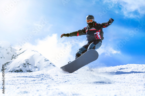 Foto op Canvas Wintersporten Jumping snowboarder from hill in winter