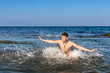 Naked young man jumping for joy from see water