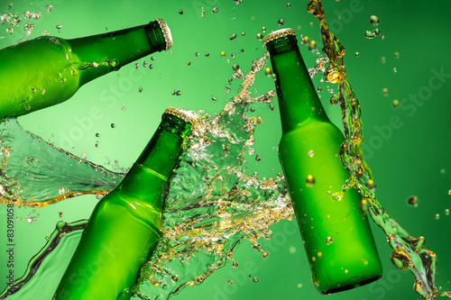 Foto op Aluminium Spa Bottles of beer with splash, on green background