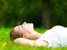 Young Woman Lying On Grass And Relaxing In Park.