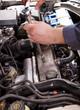 Close up of auto mechanic repairing an engine.