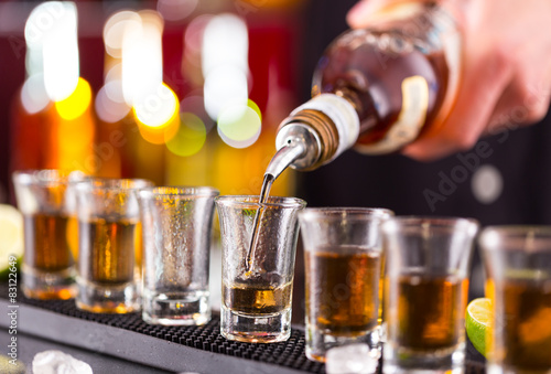 Fototapeta Barman pouring hard spirit into glasses