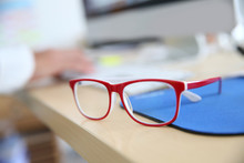Closeup Of Red Eyeglasses On Business Desk