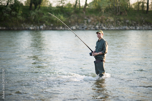 Foto op Canvas Vissen Fisherman fishing in a river