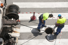 Workers Moves The Manhole Cove...