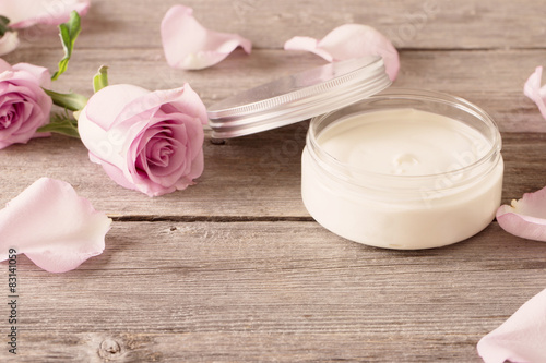 Foto  cosmetic cream with pink roses on old wooden table