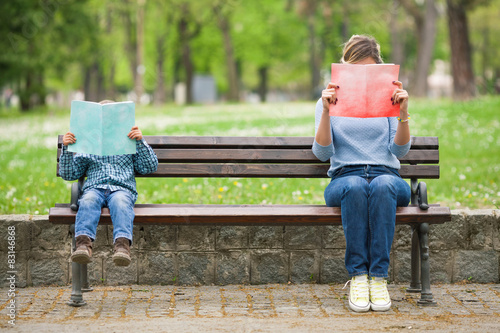 Fotografie, Obraz  Little boy and his mother sitting on a park bench reading books