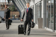 Businessman walks through airport after arriving on flight from business trip