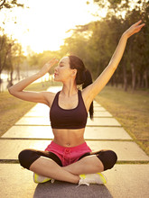 Young Asian Woman Practicing Yoga Outdoors At Sunset