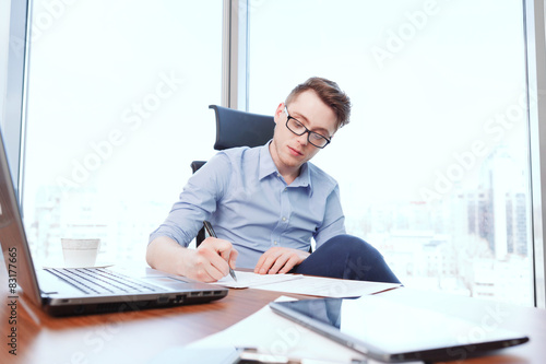 Garden Poster Young businessman filling papers in office