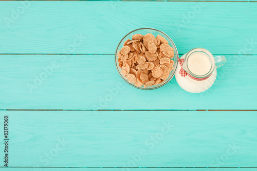 Fotografie, Tablou  Jug of milk and muesli on blue wooden table. Top view