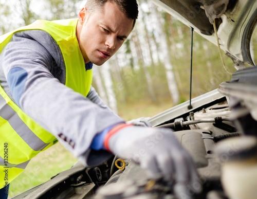 Photo Man fixing broken car on a roadside