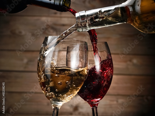 Fényképezés  Red and wihite wine pour on wood background