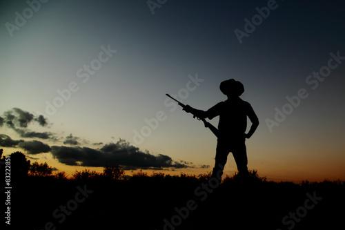 Poster Chasse Silueta de vaquero cazador al atardecer