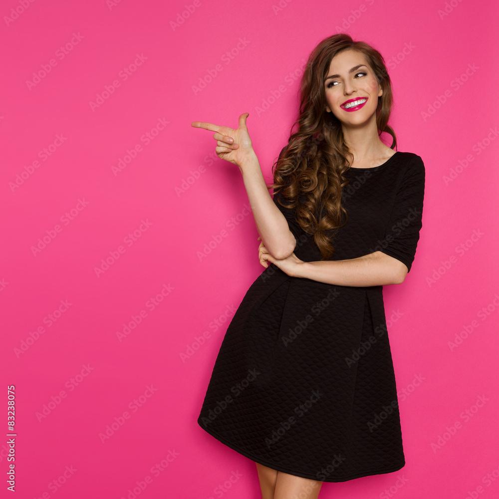 Fototapeta Fashion Model In Black Dress Pointing