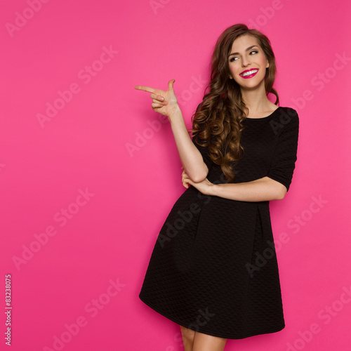 Obraz Fashion Model In Black Dress Pointing - fototapety do salonu