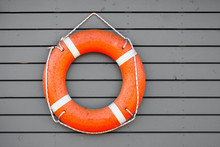 Red Lifebuoy Hanging On Gray Wooden Wall