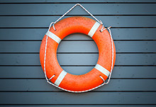 Red Lifebuoy Hanging On Blue W...