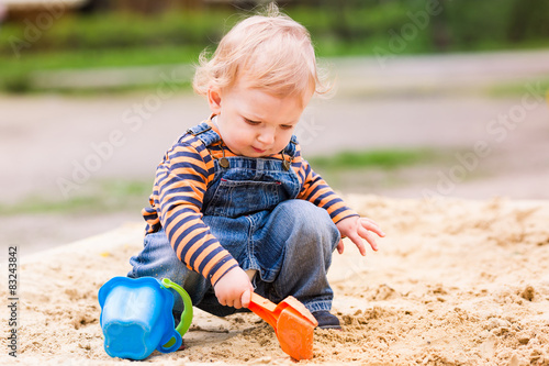 Cute baby boy playing with sand Wallpaper Mural