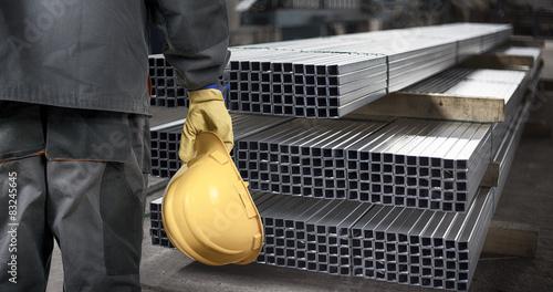 Fotomural worker with helmet in front of steel metal profiles