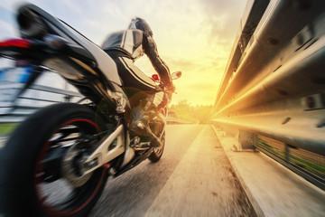 Fototapeta Motor Moto da strada sfreccia vicino al guard rail al tramonto