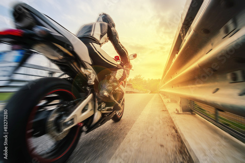 Moto da strada sfreccia vicino al guard rail al tramonto Tablou Canvas