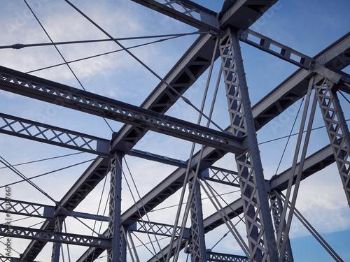 Fotografie, Obraz  Detail of painted riveted bridge against blue sky.