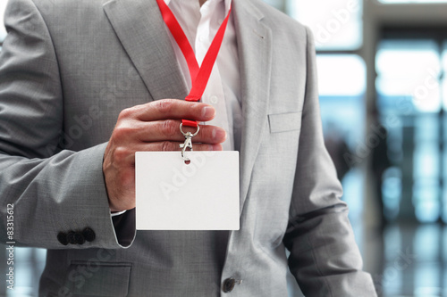 Fotografia  Businessman holding blank ID badge