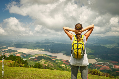 Obraz Portrait of happy traveler woman with backpack standing on top o - fototapety do salonu