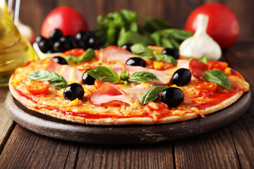 Delicious fresh pizza on brown wooden background