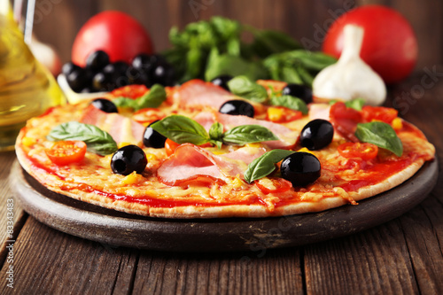 Valokuva  Delicious fresh pizza on brown wooden background