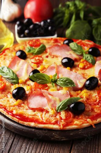 Fotografija  Delicious fresh pizza on brown wooden background