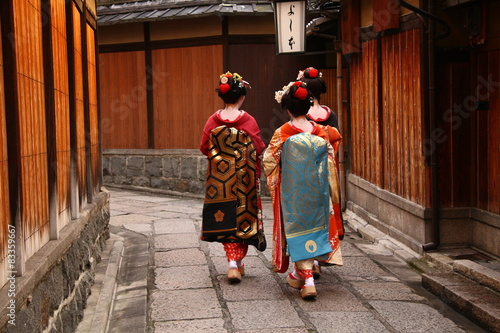 In de dag Kyoto Three geishas walking on a street of Gion (Kyoto, Japan)