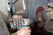 Service man worker replace car hub bearing in garage workshop