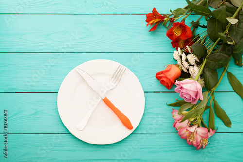 Fotografie, Tablou  Romantic dinner with flowers on blue wooden table at the restaurant