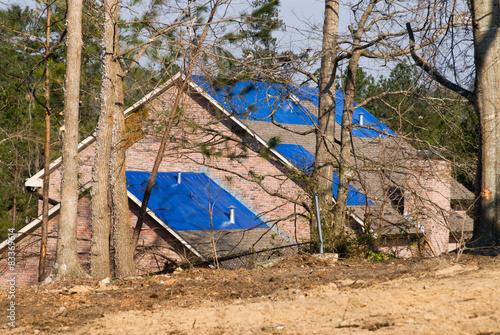 Fotografie, Obraz  tornado damaged house with a blue tarpaulin on the roof