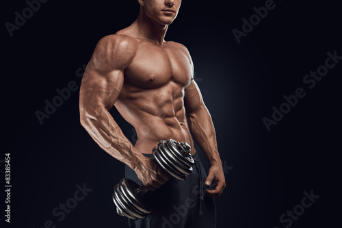 Fotografiet  Strong and power bodybuilder doing exercises with dumbbell