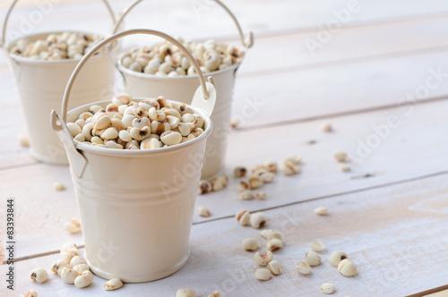 Tablou Canvas Job's tears in white bucket on wooden board, healthy food