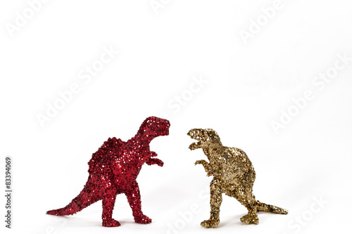 Photo  Dinosaurs in red and gold glitter on white. Landscape.