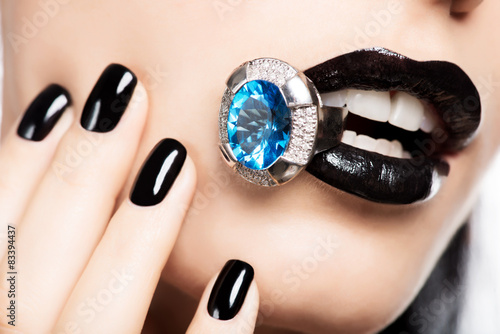 Macro shot of a woman's lips and nails painted bright color blac Poster
