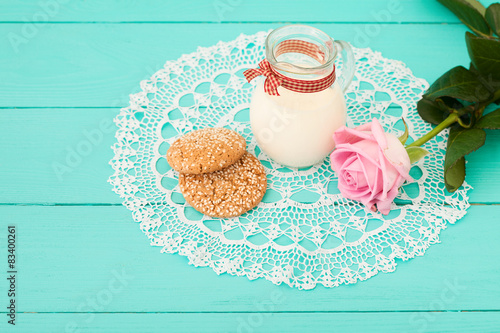 Fotografie, Tablou  Breakfast with jug of milk and cookies near rose on lace napkin