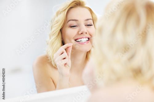 Fotografie, Obraz  Žena pomocí dentální nitě