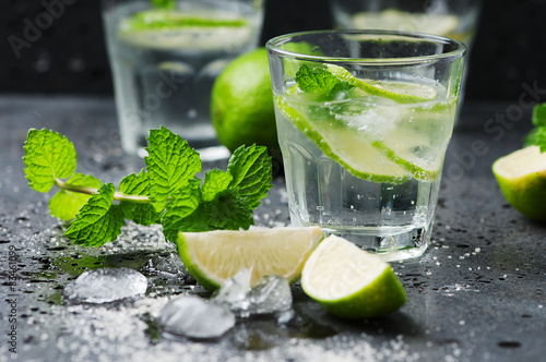 Fotografering  Mojito cocktail in a bur on a rustic table